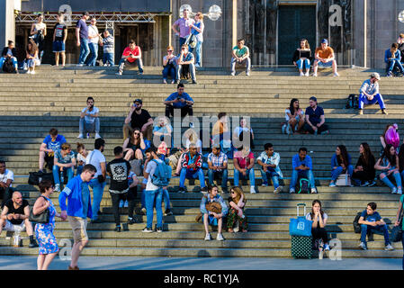 Cologne, Germany. People sitting on the stairs next to Cologne central station waiting for trains. - Stock Photo