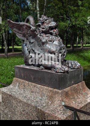 Sculpture of a lion with wings in Chinese style on a close-up bridge in the Alexander Park in Tsarskoye Selo in St. Petersburg - Stock Photo