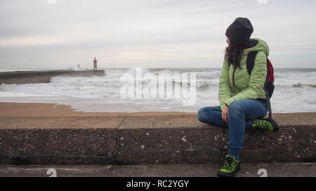 Tourist girl with backpack watching Porto light house at the Atlantic coastline - Stock Photo