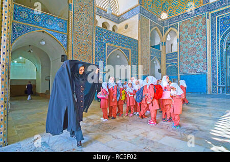 YAZD, IRAN - OCTOBER 18, 2017: The group of little schoolgirls in bright Muslim uniform and their teacher during excursion to Jameh Mosque - main hist - Stock Photo