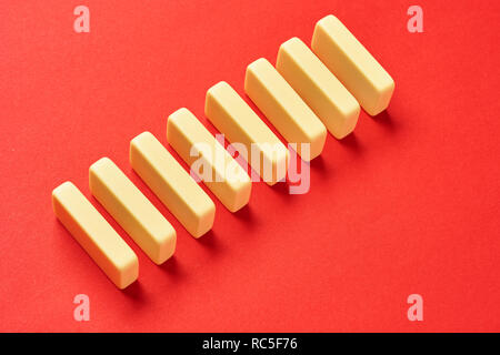White dominoes stand in row against red background as a symbol of a coherent task or the subsequent reactions of various ideas and tasks. - Stock Photo