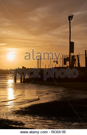 The infrastructure of Goodwood Island Wharf in silhouette, with a golden sky, and reflection off Clarence River's surface; as the sun sets in summer. - Stock Photo