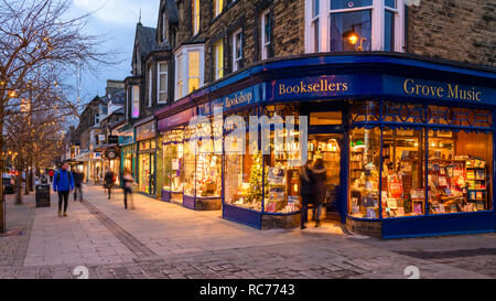 Golden glow of lights & attractive window display, exterior of The Grove Bookshop is welcoming as people walk in or past - Ilkley, West Yorkshire, UK. - Stock Photo