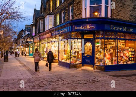 Golden glow of evening lights & attractive window display, exterior of The Grove Bookshop is welcoming (people walk past) - Ilkley, West Yorkshire, UK - Stock Photo