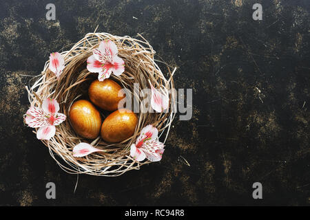 Golden Easter eggs in a nest decorated with flowers on a dark rustic background. Top view, copy space - Stock Photo
