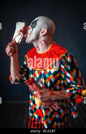 Scary bloody clown licks the knife blade. Man with makeup in halloween costume, crazy maniac holds human hand - Stock Photo