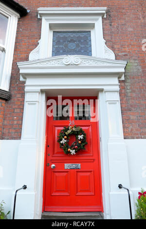 Christmas wreath with ribbon bow and baubles on the outside of a red door in Shrewsbury Shropshire England UK  KATHY DEWITT - Stock Photo