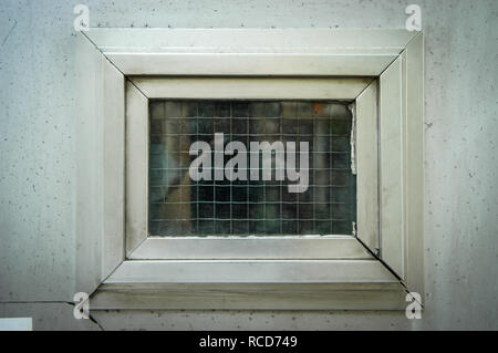 Tiny plastic Window with safety glass set into a white wall of a house - Stock Photo