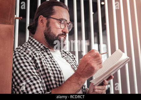Man making important notes to his notebook - Stock Photo