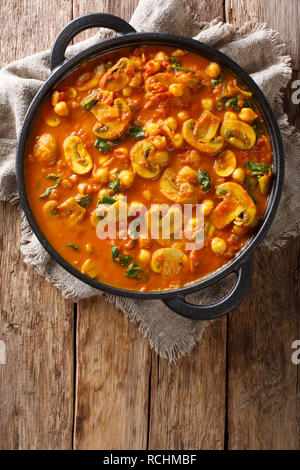 Mushroom curry with spinach and chickpeas close-up in a frying pan on the table. Vertical top view from above - Stock Photo