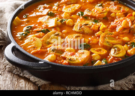 Freshly cooked mushroom curry with spinach, tomatoes and chickpeas close-up in a frying pan. horizontal - Stock Photo