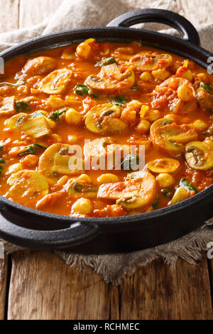 Spicy vegetarian mushroom curry with spinach and chickpeas close-up in a frying pan on the table. vertical - Stock Photo