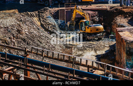 Hydraulic Excavator or wheel backhoe working in mining industry, mining activities, mine operations, quarry operations - Stock Photo