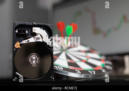 hard drive in background of dart Board with Darts at targets and graphics - Stock Photo