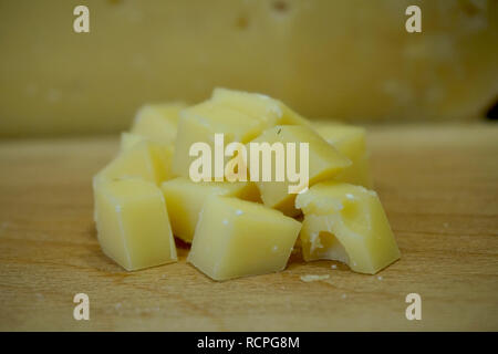 Closeup of Dutch cheese cubes with holes, on a wooden cutting board, with a larger cheese wheel showing in the background. - Stock Photo
