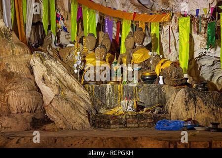 Buddhist shrine in Tham Pha In cave near Thakhek Laos - Stock Photo