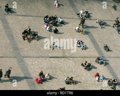 Place Georges Pompidou, Beaubourg, Paris, France: tourists sit in the Spring sun opposite the Pompidou Centre - Stock Photo