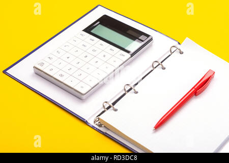 Top view of working space table with calculator, notebook and pen isolated on yellow background - Stock Photo