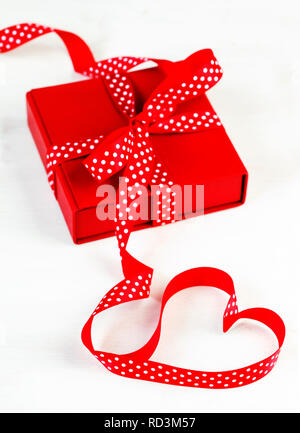 Gift box with red bow ribbon and heart shape ribbon - Stock Photo