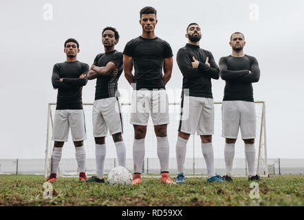 Soccer players standing together with arms crossed on a soccer field. Low angle view of football players standing on soccer field during practice. - Stock Photo