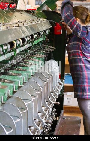 Highly skilled Swedish woman using restored wool and textile machines from 19th century to run a production line of sustainably produced wool and textile products . - Stock Photo