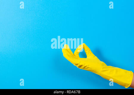 Woman hand with yellow rubber glove making a gesture meaning ok, top view on blue background - Stock Photo