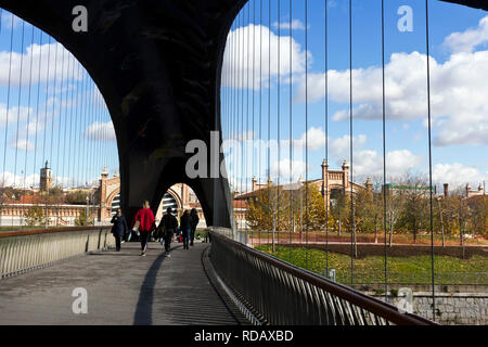 Madrid, Spain - November 23, 2018: People walk along the Matadero bridge on Manzanares river. In the background Matadero Madrid cultural center. Argan - Stock Photo