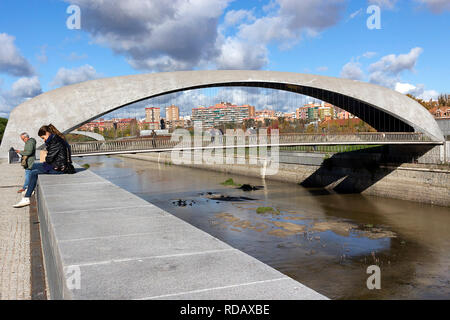 Madrid, Spain - November 23, 2018: people near the bridge Puente de Matadero on Manzanares River. The  Madrid Rio Park is a green area for sports and - Stock Photo