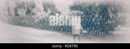 Blurred background, a woman walks with an umbrella down the street in snowy weather. Winter season. Cityscape. Banner for design. - Stock Photo