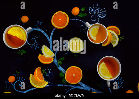 Lemon tea chalk tree with teacups, oranges and lemon slices, mint leaves and kumquats. Hot drink creative flat lay on a dark background with copy space - Stock Photo