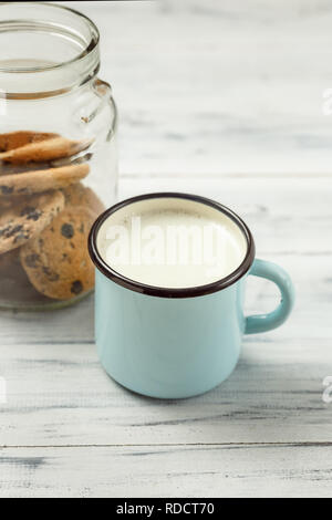 Chocolate chips cookies and a glass of milk on a white wooden background - Stock Photo