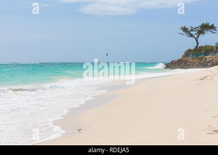 A white beach at Silver Sands on Barbados. Ocean waves roll in. Kitesurfers play in the safe waters off-shore. - Stock Photo