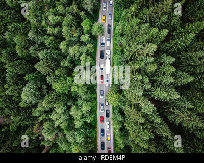 Traffic jam on a road in the middle of a forest. Top down view of cars stuck in traffic. Aerial view shot with a drone (composite photo) - Stock Photo