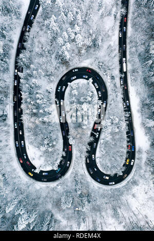 Traffic Jam on a highway trough the mountains. Aerial view of a rush hour traffic after a heavy snowfall. Winter weather and winter traffic conditions - Stock Photo