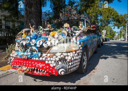 KEY WEST, FLORIDA, USA - JANUARY 14, 2019: A car decorated with a unique mix of shells and figurines stands parked on a quiet residential street. - Stock Photo