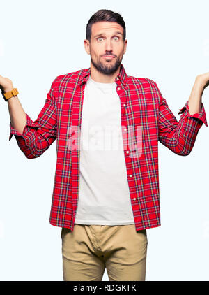 Handsome man wearing casual shirt clueless and confused expression with arms and hands raised. Doubt concept. - Stock Photo