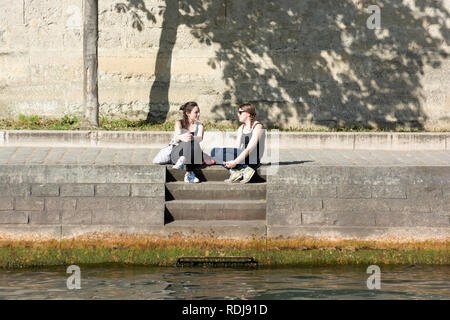 Young people are sitting along the embankment of the Canal St-Martin in Paris, France. - Stock Photo