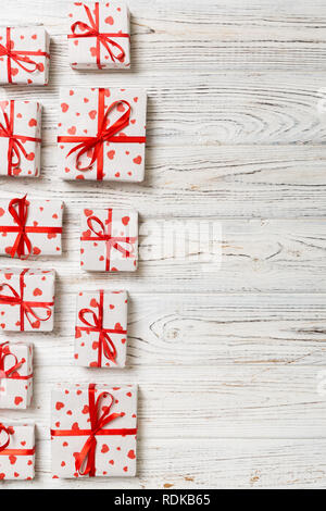 valentine or other holidays concept. Lots of Gift boxes on wood background top view. Presents in craft paper decorated with red ribbon bows and heart. - Stock Photo