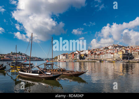 Port wine storage warehouses and transport boats at river Duoro in Vila Nova de Gaia opposite Porto, Portugal - Stock Photo