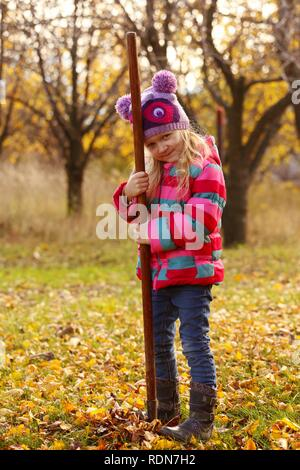 girl with rake at the autumn garden - Stock Photo