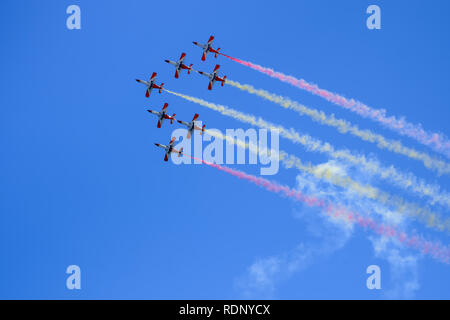 Red aircrafts aerobatic group drawing Spanish flag figure in the sky - Stock Photo