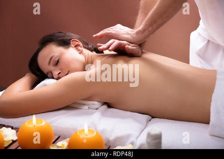 Therapist's Hand Giving Back Massage To Relaxed Young Woman In Spa - Stock Photo