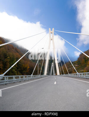 Beautiful autumn scenary with cable-stayed bridge over deep gorge in the Caucasus - Stock Photo