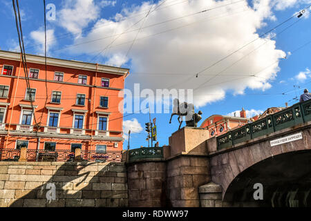 View from a canal of electrical and telephone wires crossing erratically above Anichkov Bridge and Horse Tamer sculpture in Saint Petersburg, Russia - Stock Photo