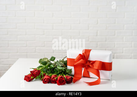 Gift box with bunch of roses on white table for Valentines Day - Stock Photo