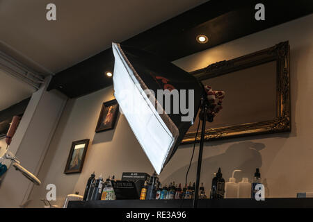 soft-box photo light inside a tattoo studio with paintings on the wall - Stock Photo