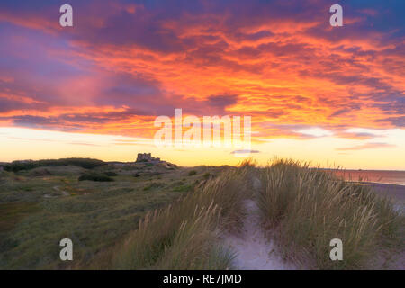 Bamburgh Castle at Sunset looking over dunes from the south side - Stock Photo