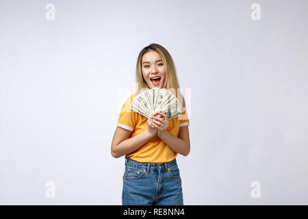 Asian woman holding cash notes isolated in white background. Young asian woman in white t-shirt in winning surprise, holding dollar note. Young rich hipster concept. - Stock Photo