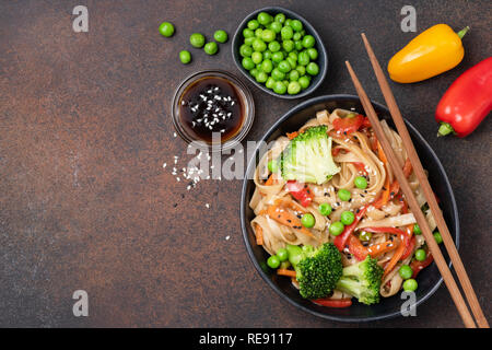 Noodles stir fry with vegetables. Udon noodles with broccoli, green pea, carrot, pepper and teriyaki sauce - Stock Photo