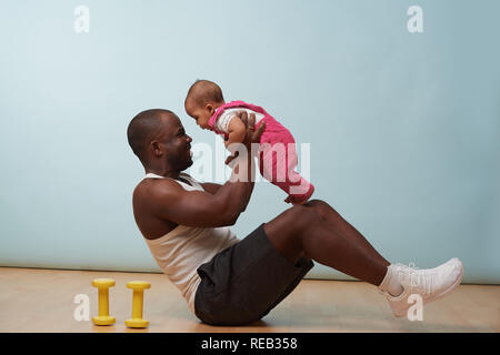 Handsome black young father is doing basic crunches while holding his tiny little baby daughter in hands. He is having trouble with additional weight. - Stock Photo